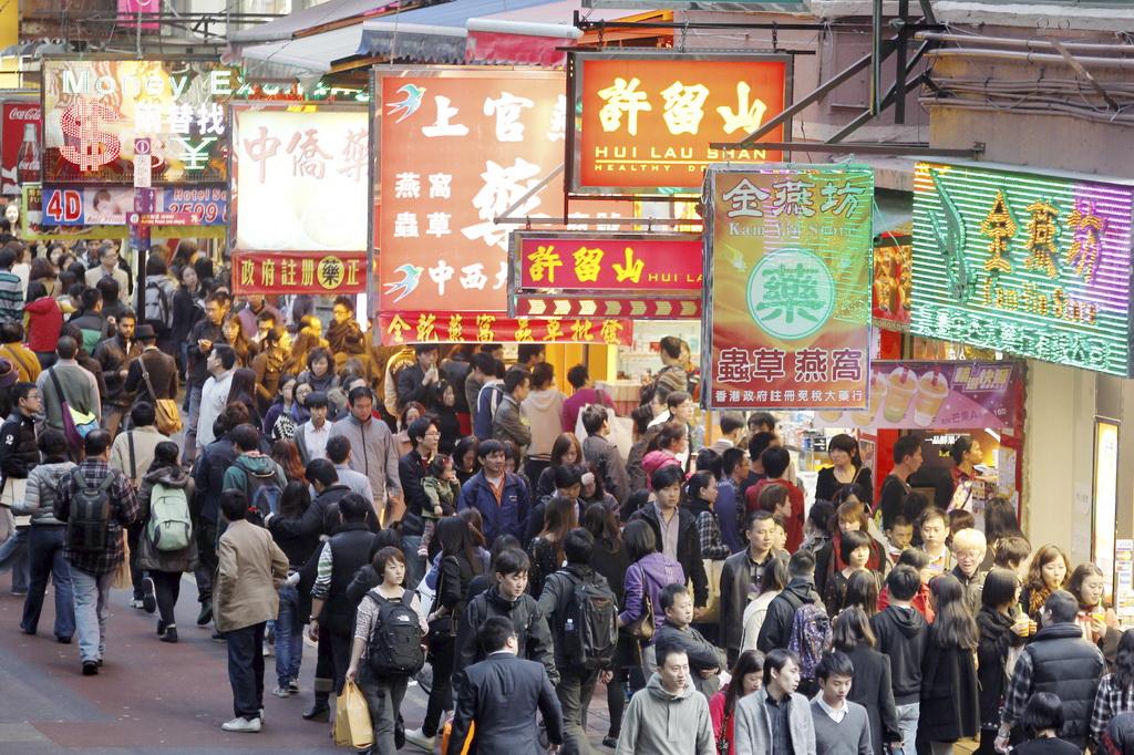 Photo d'une rue commerçante de Hong Kong, remplie de touristes