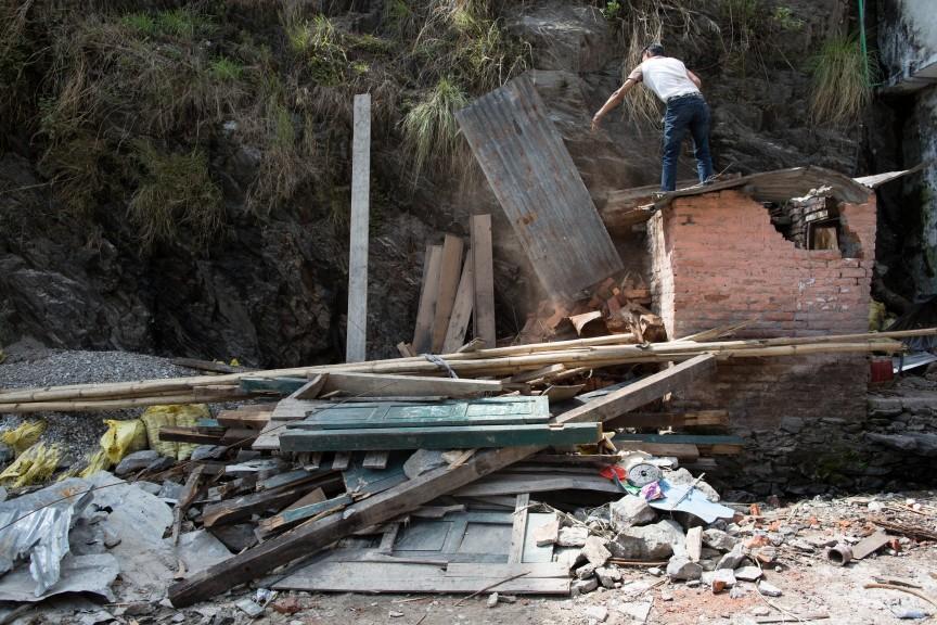 Un homme dégageant les décombres d'une maison effondrée à Kodari.