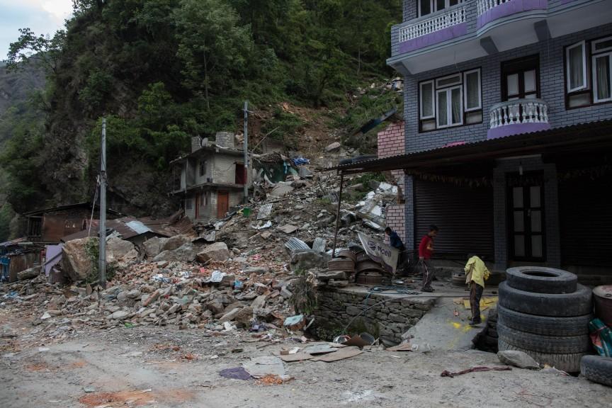 Les enfants jouent dans les décombres des maisons effondrées par un glissement de terrain, sur la route d'Araniko.