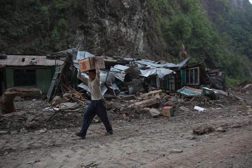 Un enfant portant des marchandises trouvées dans ce qui reste d'un camion chinois détruit par le tremblement de terre, à trente minutes à pied sur la route d'Araniko.