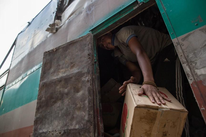 Les villageois cherchent ce qu'il reste à manger dans les camions de marchandises détruits par le séisme.