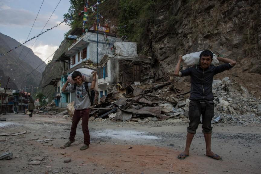 Ces hommes portent leur dernier sac de riz à partager avec les autres villageois.