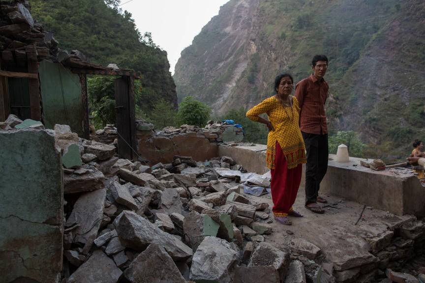 Une femme et son garçon debout, dans ce qui reste de leur maison détruite par le tremblement de terre.