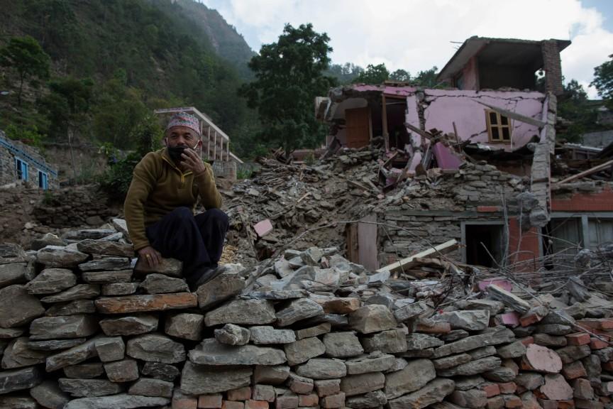 Un homme ramasse des briques dans les décombres afin de reconstruire sa maison derrière lui.