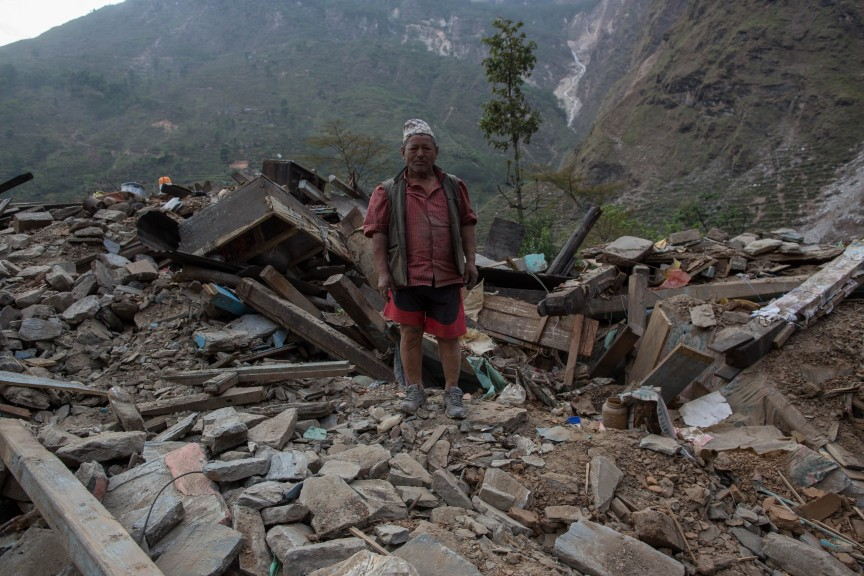 Un homme dégage les décombres de sa maison détruite.