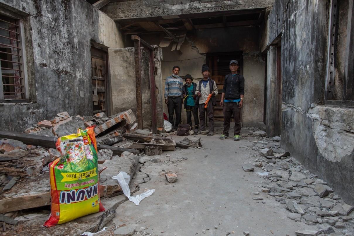Une famille à l'intérieur de sa maison détruite, sur la route d'Araniko.