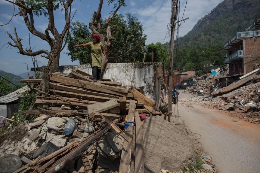 Une femme debout sur les gravats de sa maison effondrée.