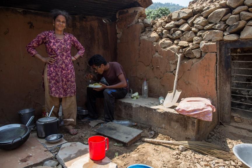 Une famille en train de déjeuner dans ce qu'il reste de sa maison détruite par le séisme.
