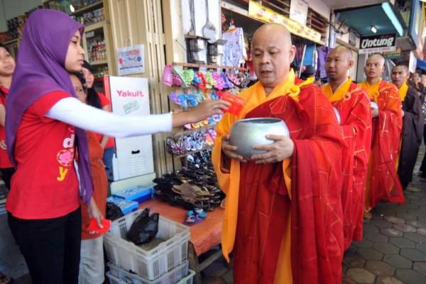 Une employée d'un magasin musulman donne l'aumône à des moines bouddhistes.
