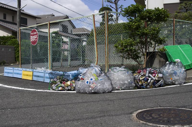Des sacs de bouteilles à recycler sont déposés sur le côté de la route.