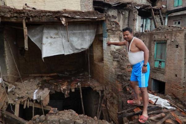 Ajay Maharjan montrant ce qui reste de sa maison à Jyako Tole, dans la ville de Harisiddhi, deux mois après le séisme du 25 avril. (Crédit : Stéphane Huët)