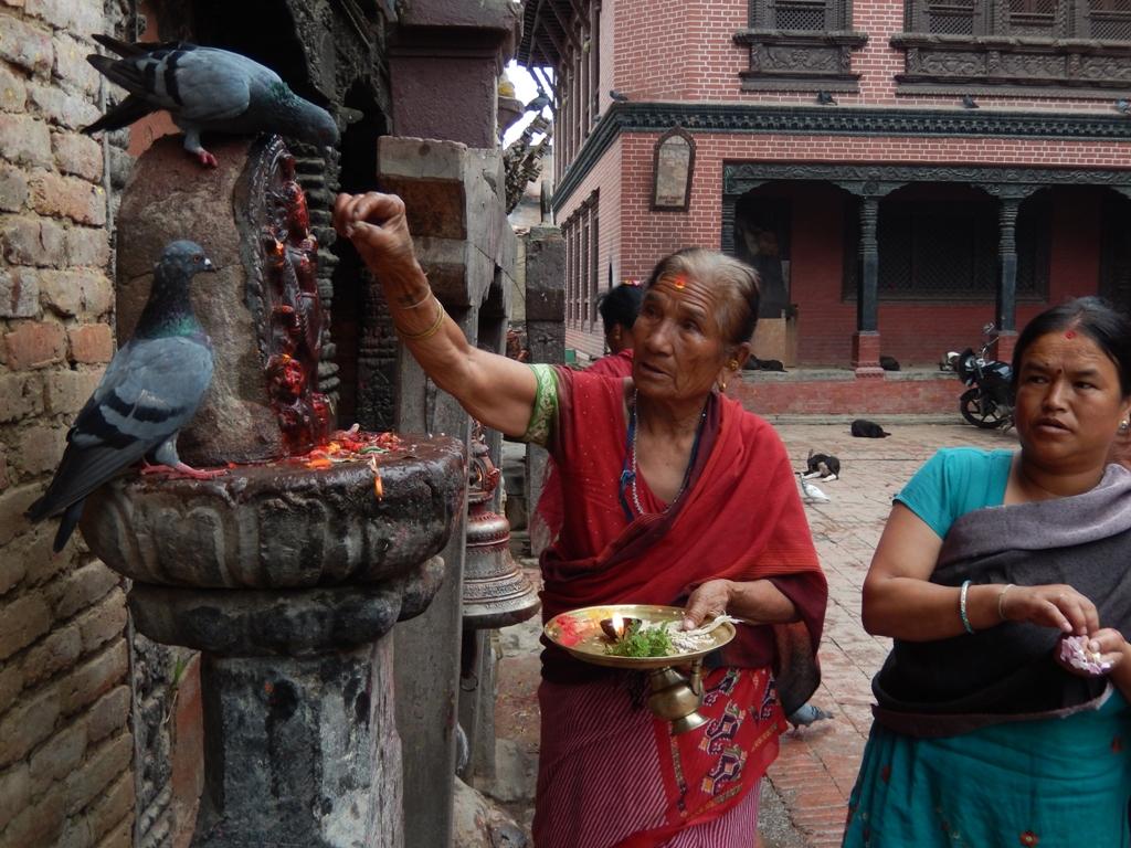 Photographie de deux femmes accomplissant leur rituel au temple