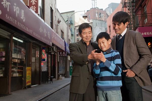 Famille utilisant un téléphone portable dans les rues de Chinatown à New-York
