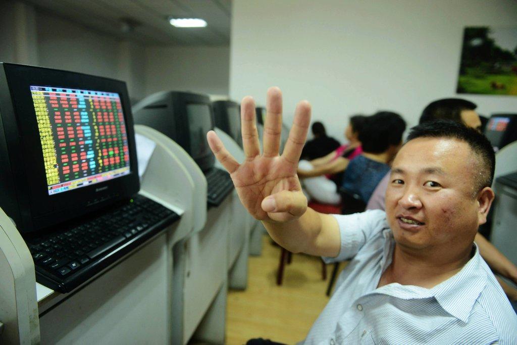 Un investisseur chinois montre le signe 4 avec sa main après que l'indice de la bourse de Shanghai ait atteint la barre des 4 000 points le 13 juillet 2015