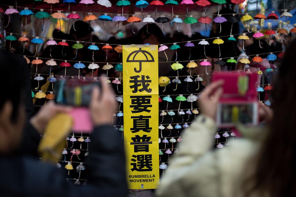 """Jeunes manifestants prenant en photos des installations de parapluies en papier symbôle du mouvement """"Occupy Central"""""""