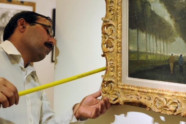 Photo d'un technicien mesurant le cadre d'un tableau
