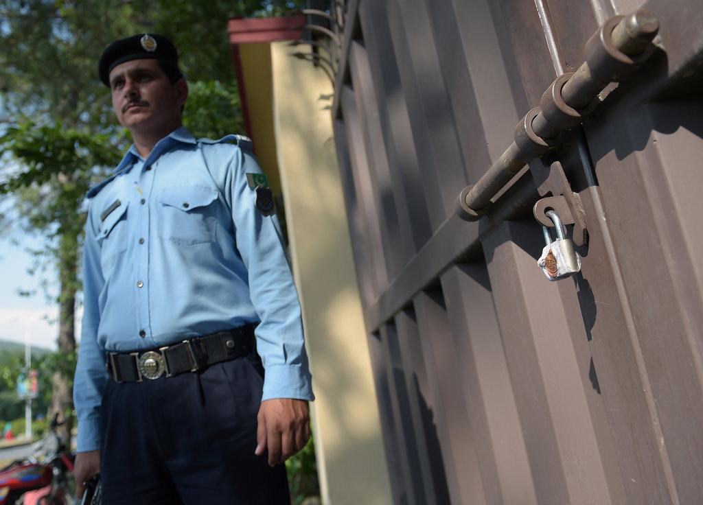 """Photo d'un policier pakistanais devant le portail cadenassé des bureaux de l'ONG """"Save the Children"""""""