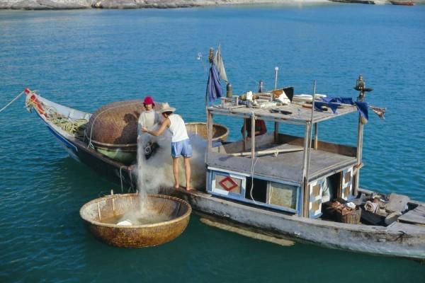 Des pêcheurs vietnamiens sortent les filets de l'une de leurs fameuses embarcations construites en tiges de canne à sucre, les thung chai