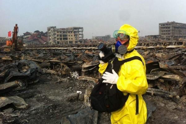 Photo d'un photojournaliste en combinaison de protection sur le site de la double explosion de Tianjin