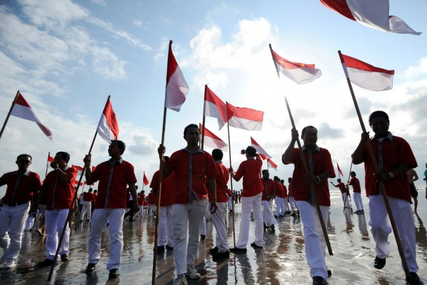 Des Balinais agitent des drapeaux indonésien lors de la célébration de l'anniversaire de l'indépendance sur une plage de Kuta