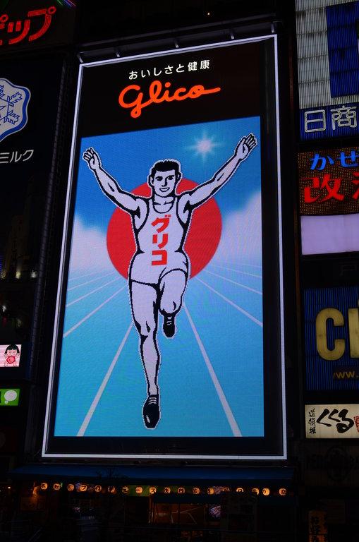 Le Glico est l'emblème de la rue Dōtonbori. Mise en place en 1935, le Glico représente un athlète sur une piste bleue symbole du confiseur Ezaki Glico L'enseigne a été modifiée plusieurs fois jusqu'à trouver ici sa version finale avec un éclairage LED