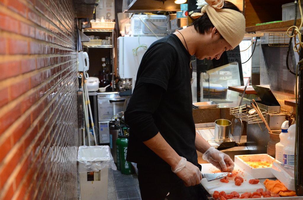 Chez Jan-Jan on propose une autre spécialité culinaire d'Osaka : des kushikatsu. Ce sont des brochettes panées. On voit ici le cuisinier préparer les ingrédients dans son étroite cuisine, typiquement nippone