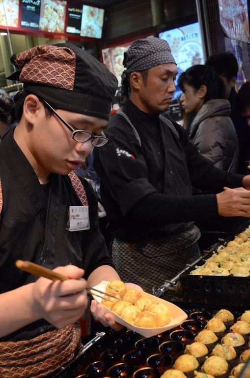 Les échoppes de takoyaki comme celle-ci à Dōtonbori sont prises d'assaut le soir venu par des touristes et des habitués