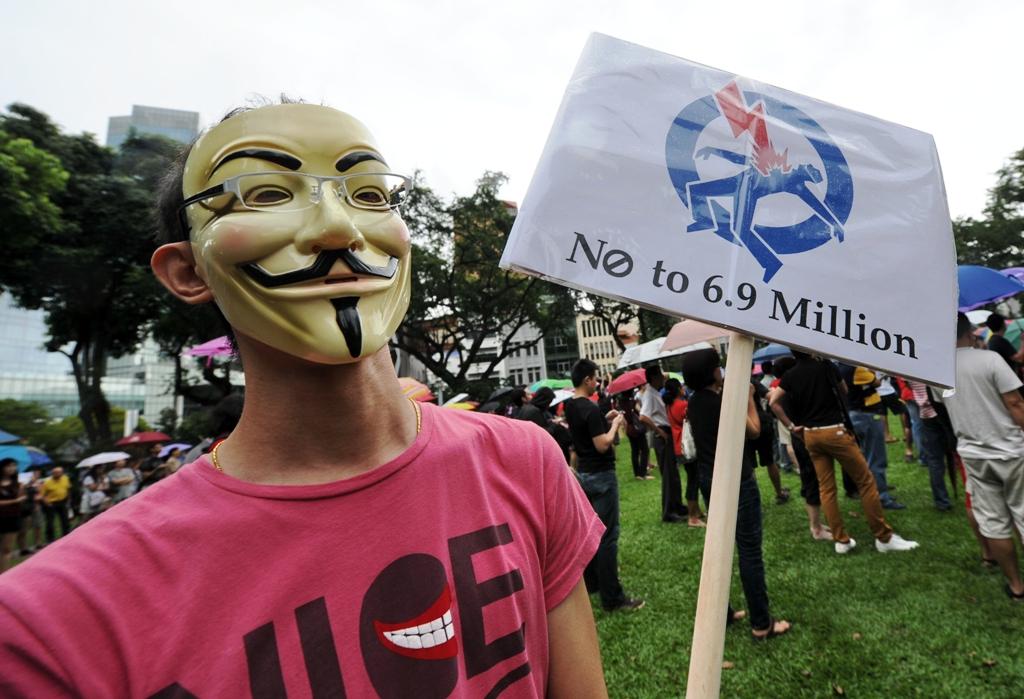 Un Singapourien portant un panneau anti-immigration lors d'un rassemblement à Siungapour le 16 février 2013. Une manifestation appelant au ralentissement de l'immigration dans la cité-Etat, suite à l'annonce du gouvernement, selon laquelle la population locale a grimpé de 30 % à près de 7 millions d'habitants en moins de 20 ans, tandis que la natalité est au plus bas