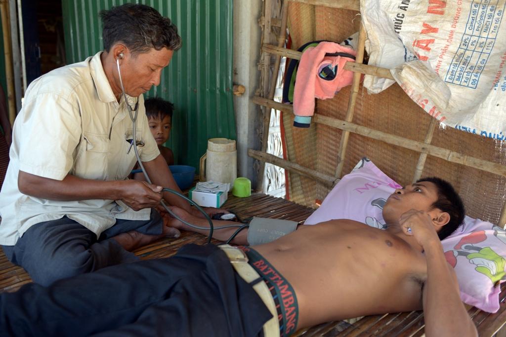 Ken mon, médecin sans licence, prend la tension artérielle d'un patient, dans un village de la province de Kampong Speu au Cambodge. (Crédit : TANG CHHIN SOTHY / AFP)
