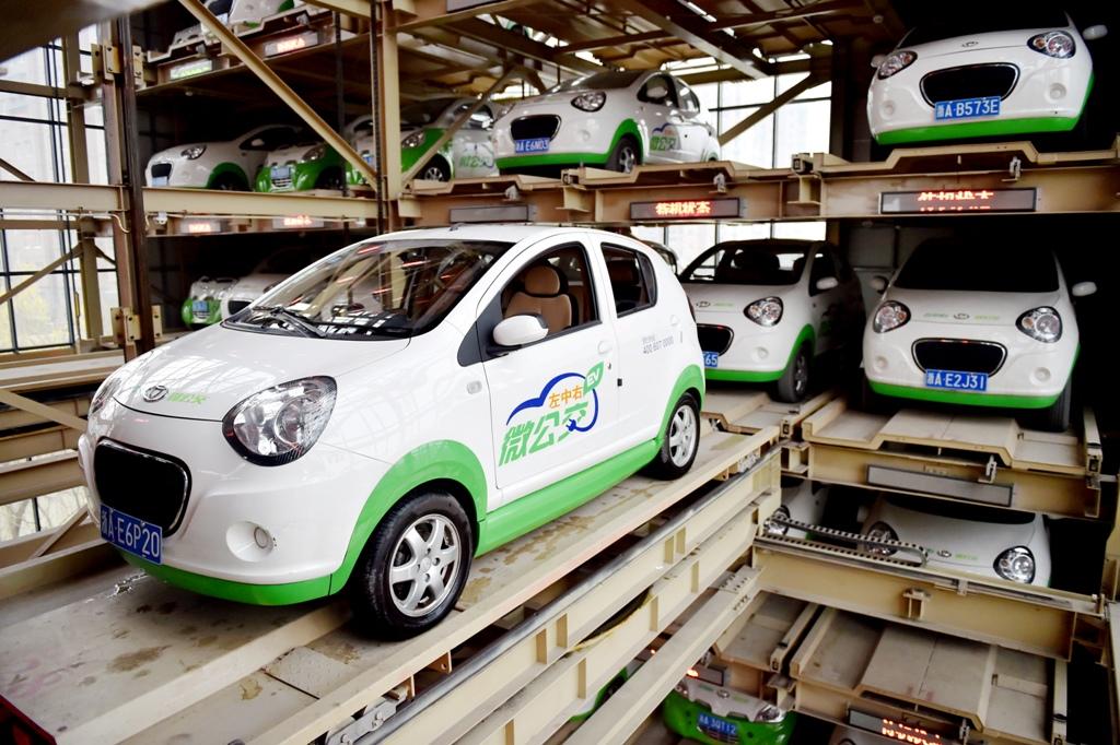 Voitures électriques à louer, garées verticalement dans une station de Hangzhou, capitale du Zhejiang, riche province côtière de l'Est chinois, le 5 janvier 2015. La location de véhicules électriques est devenu de plus en plus populaire à Hangzhou depuis que la ville a instauré la circulation alternée en mars 2014. La voiture peut rouler 80 km, pleinement chargée, et la location à l'heure coûte 20 yuans, soit 2,80 euros. (Crédit : Liang zhen / Imaginechina / via AFP)