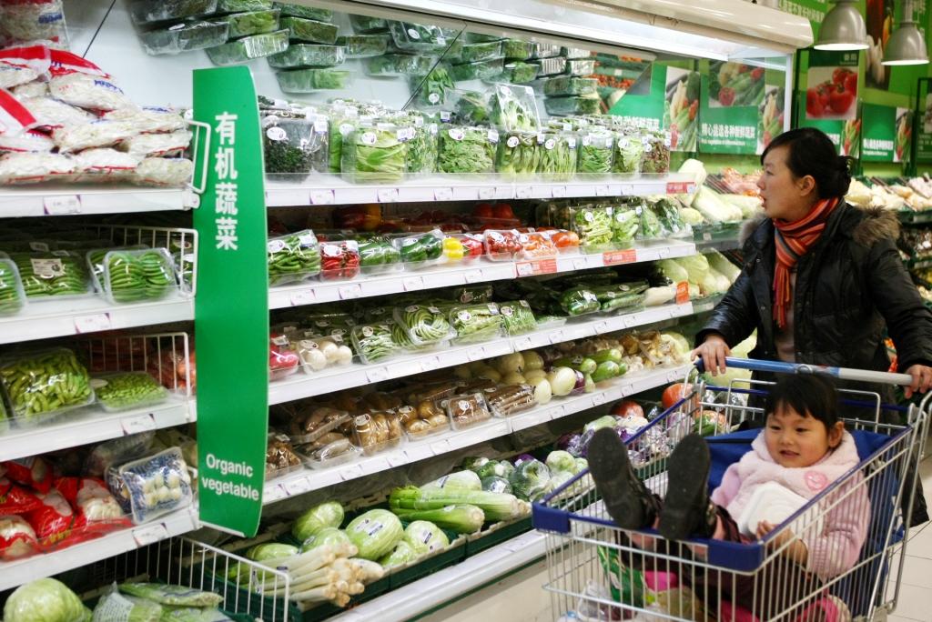"""Une Chinoise pousse son bébé devant le rayon """"légumes bio"""" dans un supermarché Tesco à Shanghai, le 6 janvier 2009. (Crédit : Shanghai Daily / Imaginechina / via AFP)"""