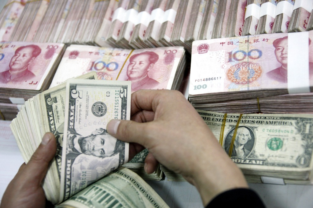 Un employé de banque chinois compte des billets en dollars et en yuans dans une banque de la ville de Huabei, dans la province de l'Anhui, à l'est de la Chine, le 13 janvier 2011. (Crédit : Xie zhengyi / Imaginechina / via AFP)