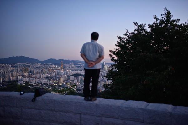 Un coréen pensif devant la skyline de la ville de Séoul le 7 septembre 2015. (Crédit: Ed Jones / AFP).