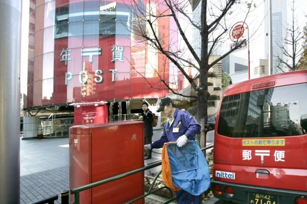 Un facteur collecte le courrier près d'une station de métro à l'apparence d'une gigantesque boîte aux lettres, à Tokyo le 15 décembre 2008. (Crédit : AFP PHOTO / Yoshikazu TSUNO)