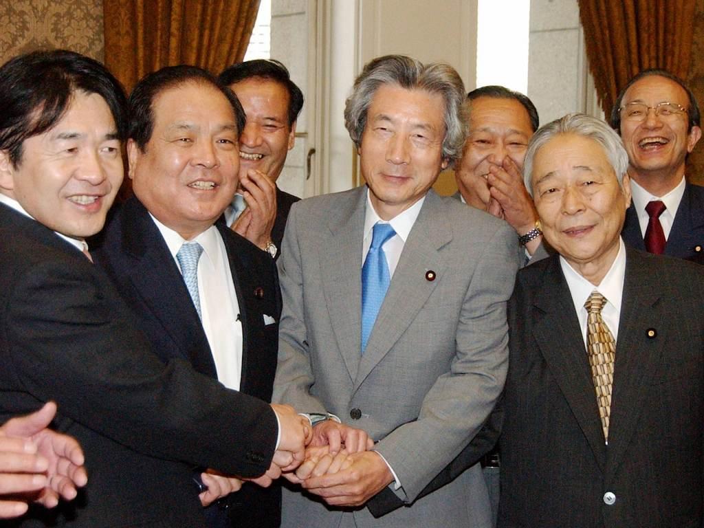 Le 14 octobre 2005, Junichiro Koizumi, alors Premier ministre japonais célèbre avec les dirigeants de son parti le Jiminto (Parti Libéral-démocrate, conservateur) le vote par la Chambre Haute des planbs de privatisation de la Poste. (Crédit : AFP PHOTO/JIJI PRESS)