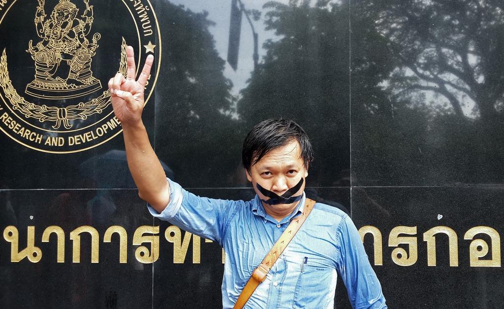 """Le journaliste thaïlandais Pravit Rojanaphruk devant une base militaire à Bangkok où il a été convoqué le 25 mai 2014. Plus récemment, le 14 septembre 2015, un autre journaliste thaï a été arrêté par la junte pour subir un """"réajustement d'attitude"""". (STR / AFP PHOTO)"""