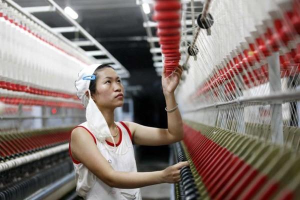 Une ouvrière chinoise sur une ligne de production de fil de laine pour l'exportation ans les pays d'Asie du Sud-Est, dan sune usine textile de Huabei dans la province chinoise côtière de l'Anhui, le 28 août 2015. (Crédit : Xie zhengyi / Imaginechina / via AFP)