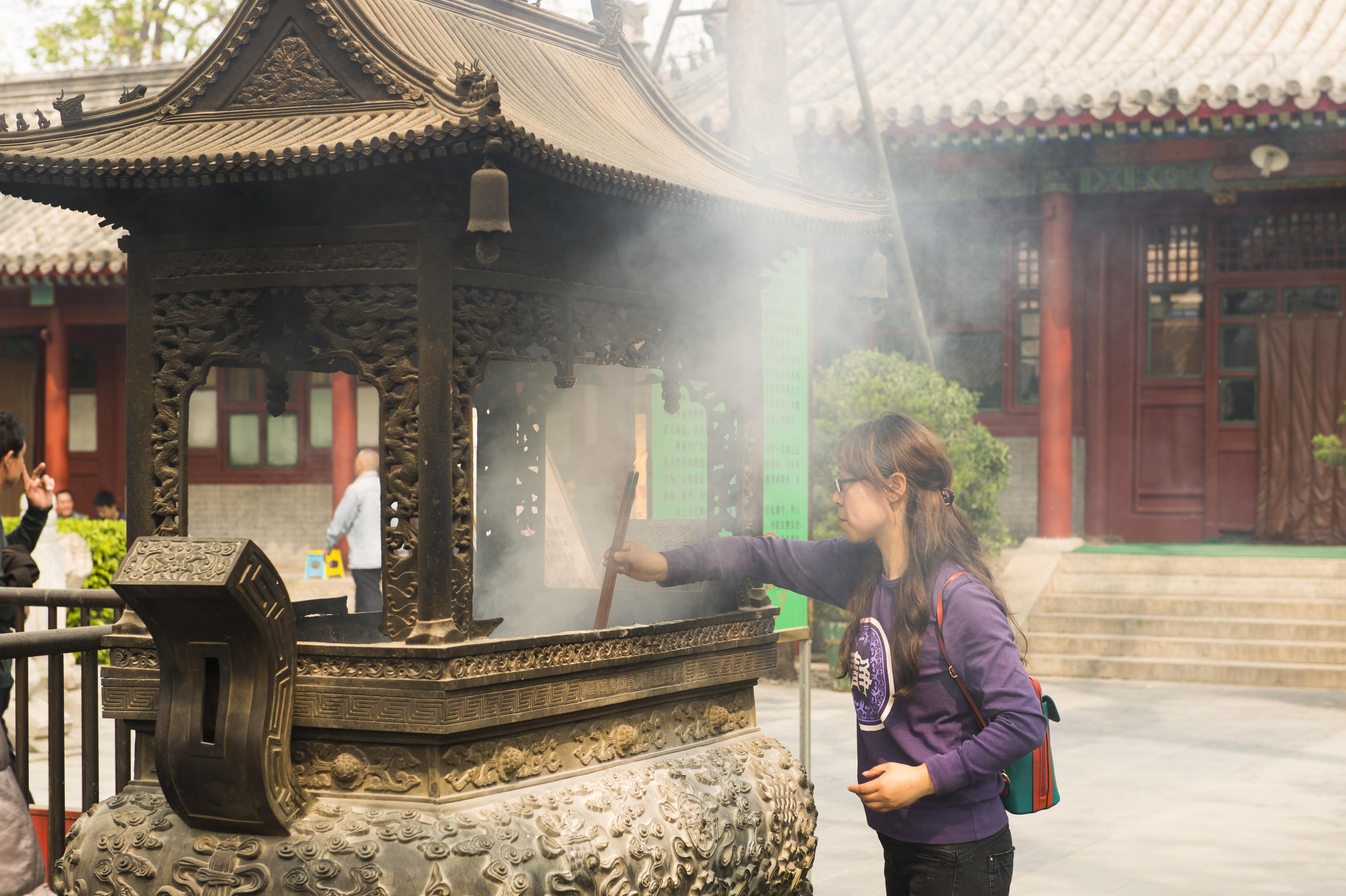 une jeune chinoise prie pour la bonne fortune au temple Guangji à Pékin, en Chine. (Crédit : Christoph Mohr / Picture alliance / Picture-Alliance / AFP).