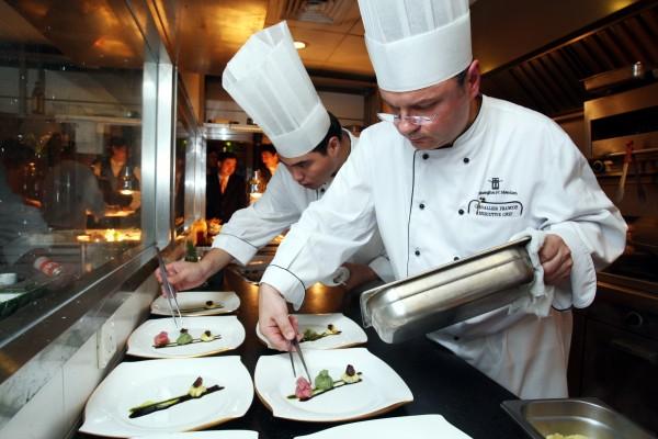 Des chefs étrangers et chinois travaillent côte à côte dans les cuisines du Shanghai JC Mandarin Hotel à Shanghai. La municipalité de Shanghai est l'une des municipalités chinoises attirant le plus grand nombre d'expatriés. (Crédit : Shanghai Daily/ImagineChina/AFP).