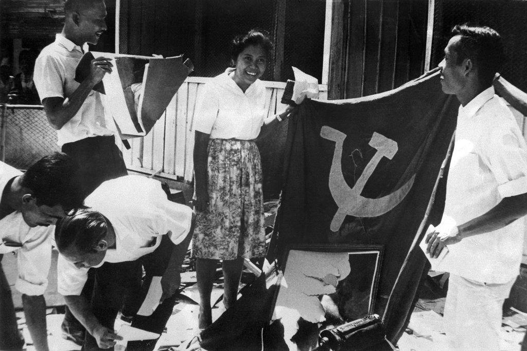 Photo datée du 21 octobre 1965 de manifestants défilant dans Jakarta avec des drapeaux nationaux en criant des slogans anti-communistes. (Crédit : AFP).
