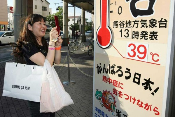 Une Japonaise prend en photo un poster géant de thermomètre indiquant 39 degrés à Kumagaya, préfecture de Saitama au nord de Tokyo, le 24 juin 2011. Cet été-là, la température avait atteint les 40 degrés pour la première fois un mois de juin. (STR / JIJI PRESS / AFP PHOTO)