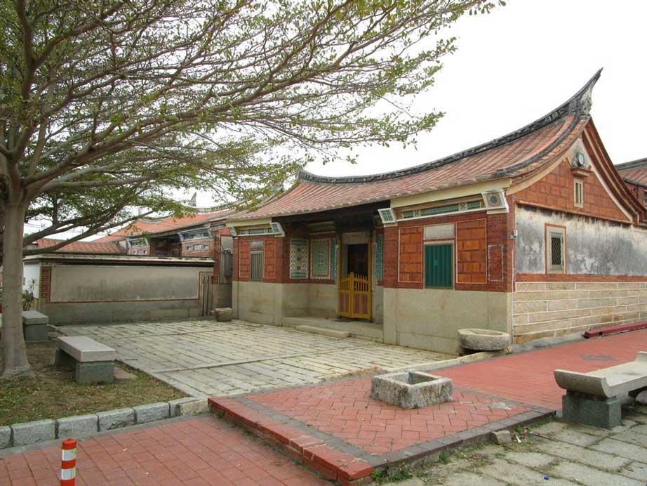 """Les habitations traditionnelles de type minnan se reconnaissent notamment à leurs murs en briques rouges et à leur toit concave dit en """"queue d'hirondelle"""" ou en """"dos de cheval"""". (Crédit : Alexandre Gandil, janvier 2015)"""