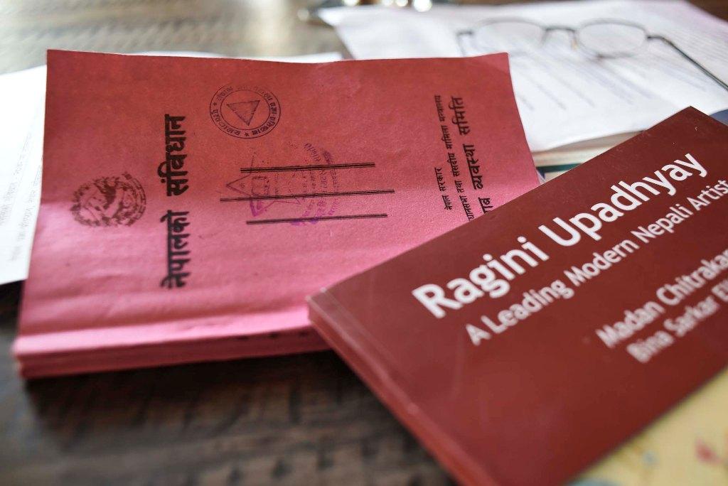 Le livret rose, nouvelle constitution népalaise et posé dessus, un livre sur Ragini Upadhyay, rectrice de l'Académie des Beaux-Arts. (Copyright : Ingrid Chiron)