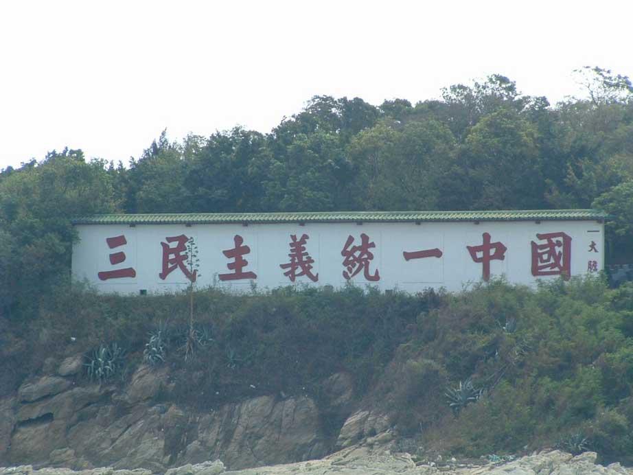 """""""La Chine est unie par les Trois Principes du Peuple"""", inscription propagandiste sur l'îlot de Dadan, faisant face au continent. (Crédit : Minsc sur zh.wikipedia GFDL ou CC-BY-SA-3.0, via Wikimedia Commons)"""