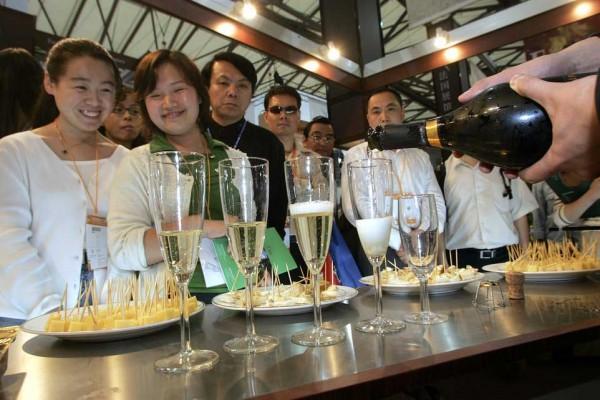 Des visiteurs admirent le service lors d'une foire internationale de la gastronomie à Shanghai en mai 2005. (Crédit : LIU JIN / AFP)