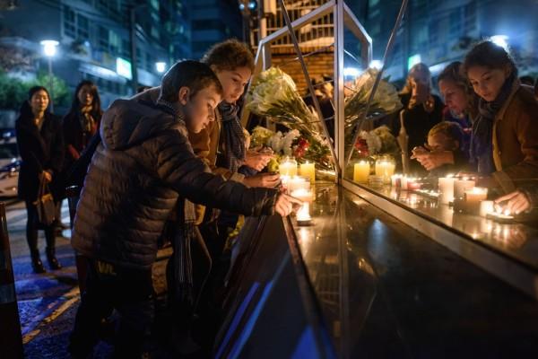 En mémoire des victimes des attentats de Paris, des Français de Séoul allument des bougies devant l'ambassade de France dans la capitale sud-coréenne, le 14 novembre 2015. (Crédit :AFP PHOTO / Ed Jones)