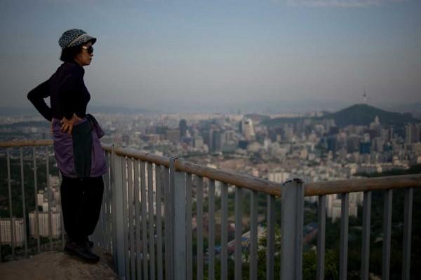 Une jeune femme se tient devant la skyline de Séoul au crépuscule. (Crédit : ED JONES / AFP).