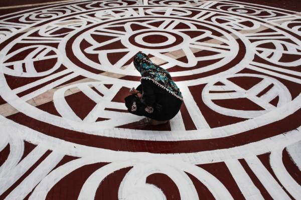 Une étudiante de l'université des Beaux-Arts de Dacca en train de peindre la cour de Shahid Minar, à Dacca le 19 février 2015.