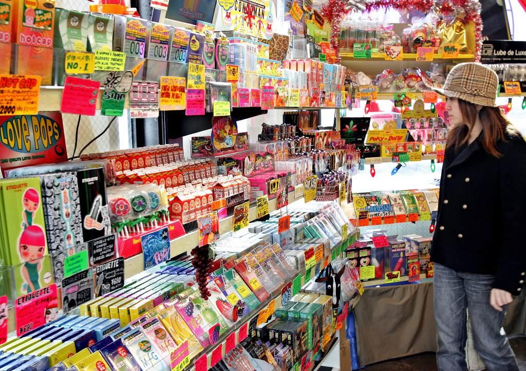 """Une cliente face à un rayon de préservatifs multicors et """"multi-packagés"""", au magasin Condomania spécialiste des préservatifs à Tokyo, le 30 Novembre 2004."""