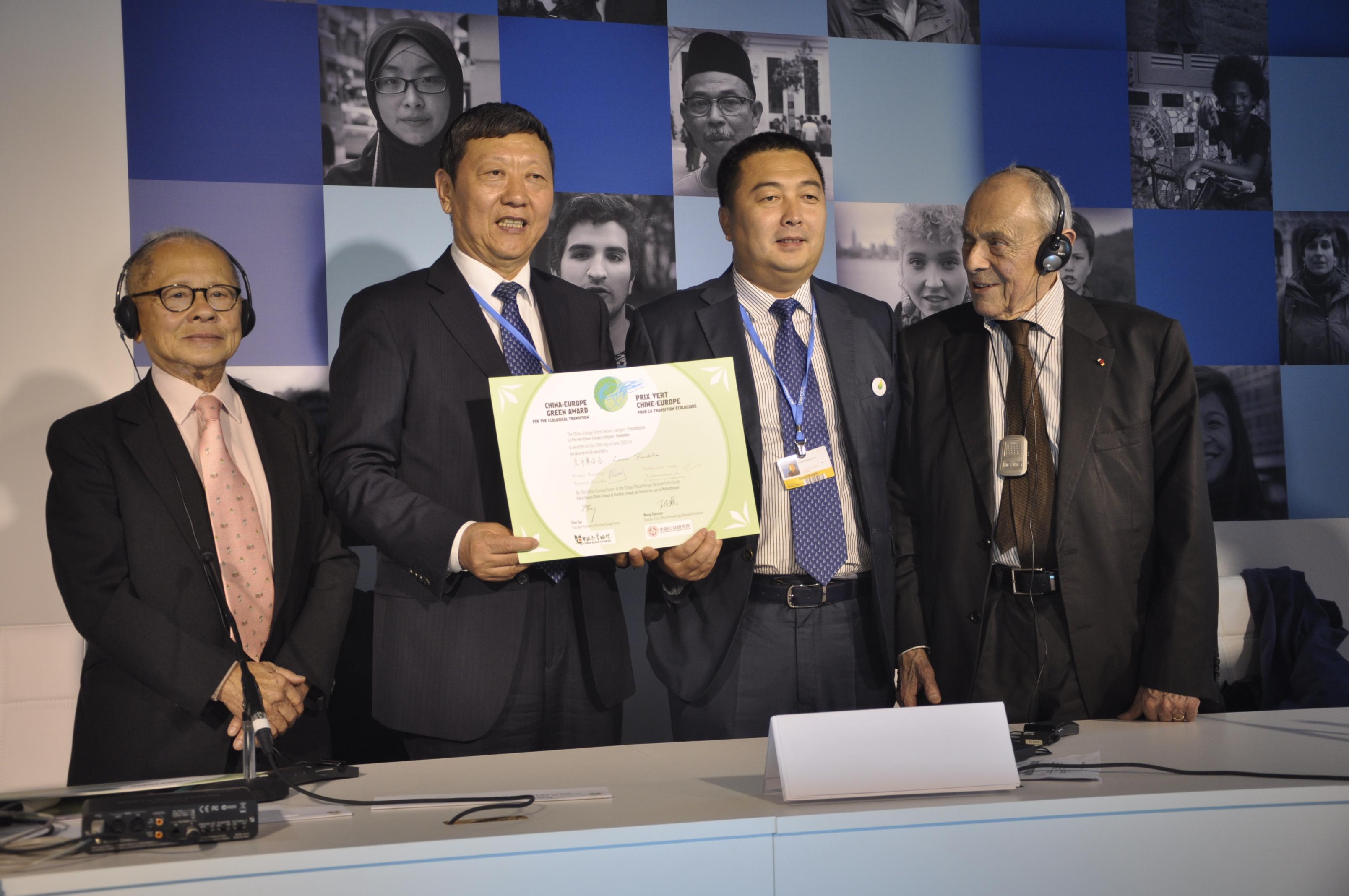 Remise du Prix Vert à Niu Gengsheng, créateur de la fondation chinoise Lao Niu, lors du side-event organisé par le Forum Chine-Europe, le 1er décembre durant la COP21 au Bourget. Il est entouré de Michel Rocard, ancien Premier ministre et de Paul Trân Van Thinh, président de l'associaiton du Forum Chine Europe.